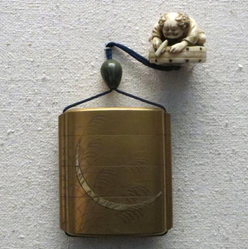 Caja o frasco metálico con un netsuke de marfil cerrando el cordón.